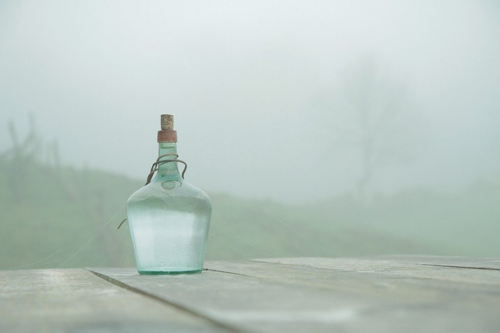 glass bottled water on a table in a foggy environment